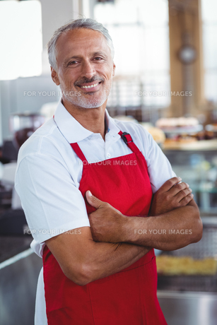 Happy barista smiling at camera with arms crossedの写真素材 [FYI00008760]