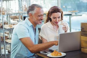 Happy couple pointing something on laptopの写真素材 [FYI00008762]