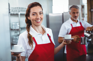 Pretty barista holding cups of coffee with colleague behindの写真素材 [FYI00008763]