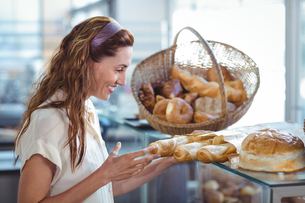 Pretty brunette pointing at loaf of breadの写真素材 [FYI00008766]