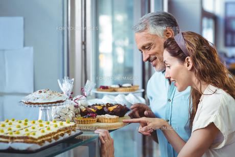 Happy couple pointing cakesの写真素材 [FYI00008771]
