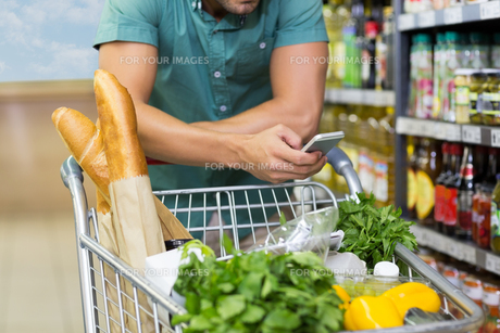 Man buy products and using his smartphoneの写真素材 [FYI00008775]