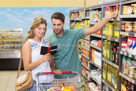 Smiling bright couple buying food productsの写真素材 [FYI00008784]