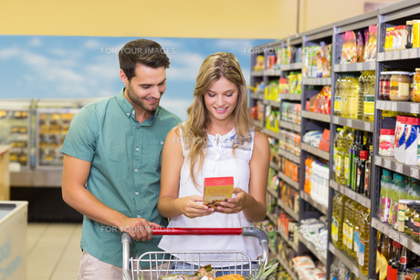 Smiling bright couple buying food productsの写真素材 [FYI00008785]