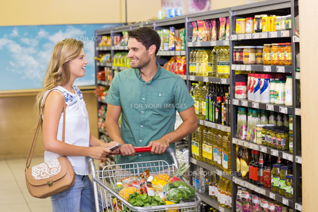 Smiling bright couple buying food productsの写真素材 [FYI00008788]