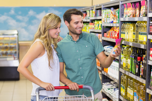 Smiling bright couple buying food productsの写真素材 [FYI00008789]