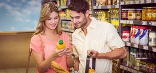 Smiling bright couple buying food products with shopping basketの写真素材 [FYI00008790]