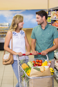 Smiling bright couple buying food productsの写真素材 [FYI00008792]