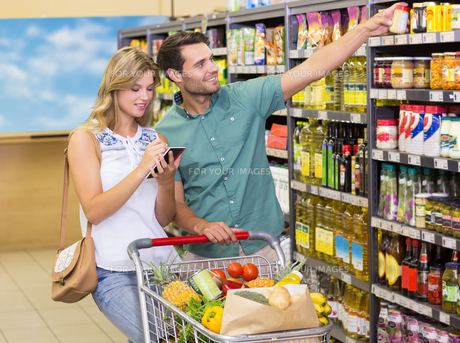 Smiling bright couple buying food products showing shelfの写真素材 [FYI00008793]