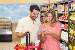 Smiling bright couple buying food products with shopping basketの写真素材 [FYI00008794]