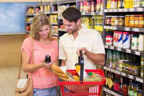 Smiling bright couple buying food porducts with shopping basketの写真素材 [FYI00008796]