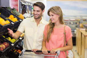 Smiling bright couple buying food productsの写真素材 [FYI00008802]
