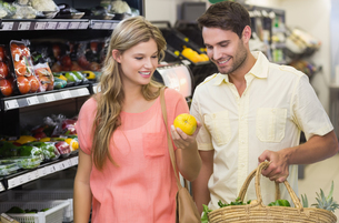 Smiling bright couple buying food productsの写真素材 [FYI00008806]