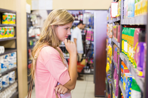 Pretty blonde woman looking at shelf and thinkingの素材 [FYI00008815]
