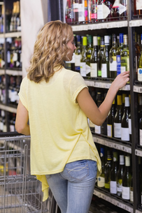 Back view of a blonde woman looking at a wine bottleの素材 [FYI00008833]