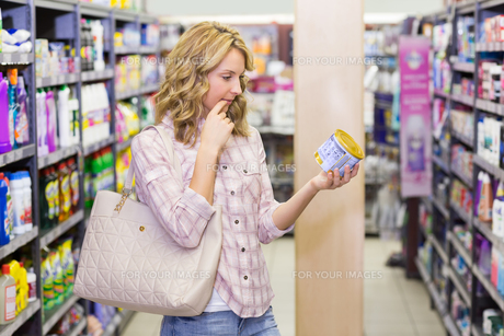 Side view of a pretty blonde woman looking at a productの素材 [FYI00008838]