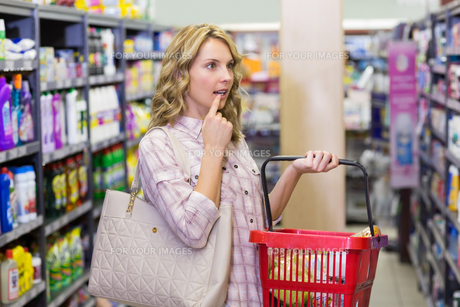 Side view of a pretty blonde woman having a shopping bag and looking at shelfの写真素材 [FYI00008844]
