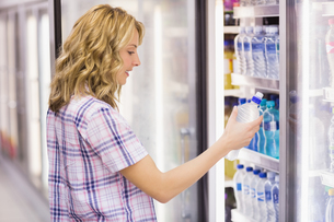 Smiling blonde woman taking a water bottleの写真素材 [FYI00008848]