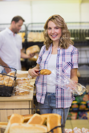 Portrait of a smiling blonde woman taking a breadの素材 [FYI00008854]
