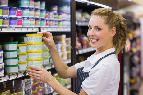Portrait of a smiling blonde worker taking a productsの写真素材 [FYI00008856]
