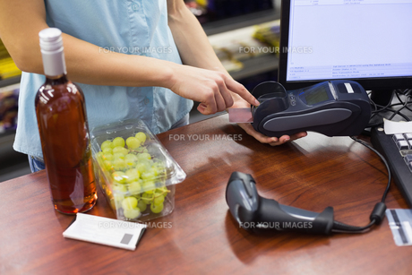 Woman at cash register paying with credit cardの素材 [FYI00008859]