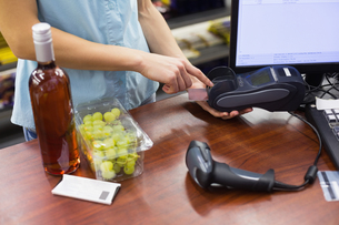 Woman at cash register paying with credit cardの写真素材 [FYI00008859]