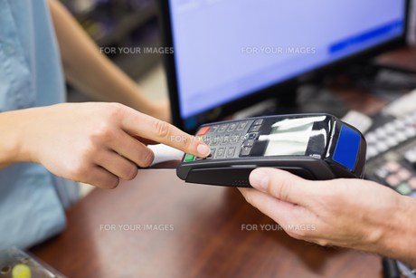Woman at cash register paying with credit cardの素材 [FYI00008860]