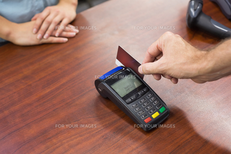 Woman at cash register paying with credit cardの素材 [FYI00008862]