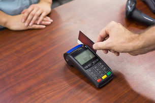 Woman at cash register paying with credit cardの写真素材 [FYI00008862]