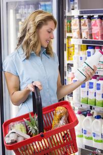 Smiling woman having on her hands a fresh milk bottleの素材 [FYI00008863]