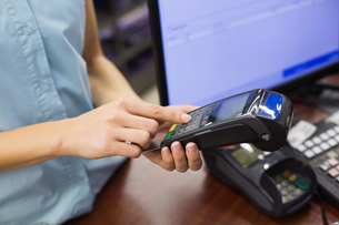 Woman at cash register paying with credit cardの写真素材 [FYI00008864]