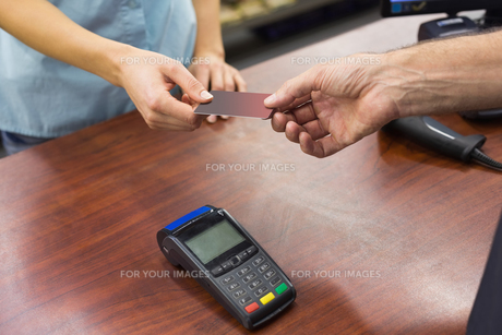 Woman at cash register paying with credit cardの素材 [FYI00008865]