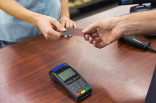 Woman at cash register paying with credit cardの写真素材 [FYI00008865]