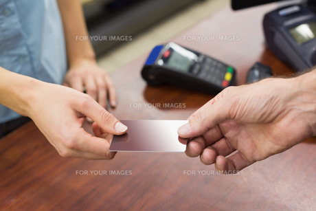Woman at cash register paying with credit cardの素材 [FYI00008866]