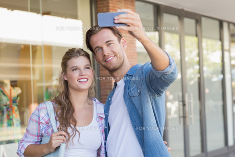 A smiling happy couple taking selfiesの素材 [FYI00008892]