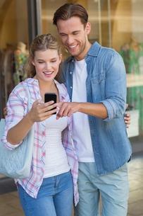 Happy couple looking at smartphoneの写真素材 [FYI00008897]