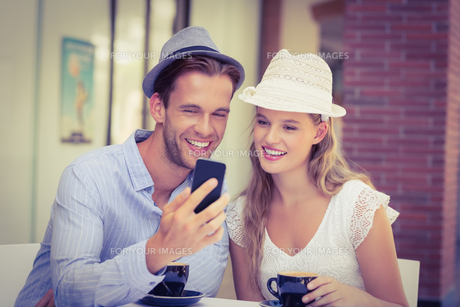 Cute couple looking at a smartphoneの写真素材 [FYI00008935]