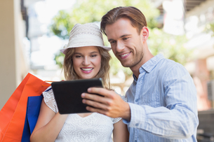 Cute smiling couple looking a tabletの写真素材 [FYI00008946]