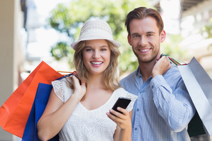 Cute couple holding shopping bagsの写真素材 [FYI00008947]