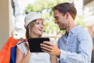 Cute smiling couple looking a tabletの写真素材 [FYI00008948]