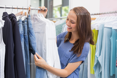 Pretty brunette browsing in the clothes rackの素材 [FYI00008950]