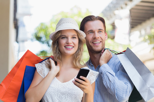 Cute couple holding shopping bagsの写真素材 [FYI00008960]