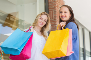 Happy friends holding shopping bagsの素材 [FYI00008965]