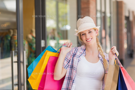 Smiling woman holding shopping bagsの素材 [FYI00008972]