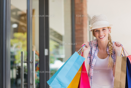 Smiling woman holding shopping bagsの素材 [FYI00008976]