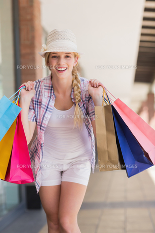 Smiling woman holding shopping bagsの素材 [FYI00008978]