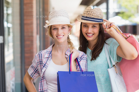 Happy women smiling at camera with shopping bagsの写真素材 [FYI00008981]