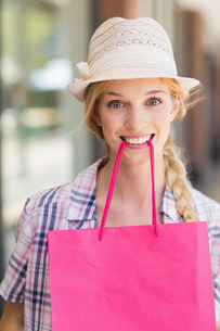 Blonde woman with shopping bag in her mouthの写真素材 [FYI00008983]