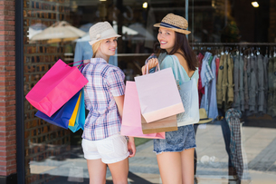 Rear view of happy women smiling at camera with shopping bagsの写真素材 [FYI00008986]