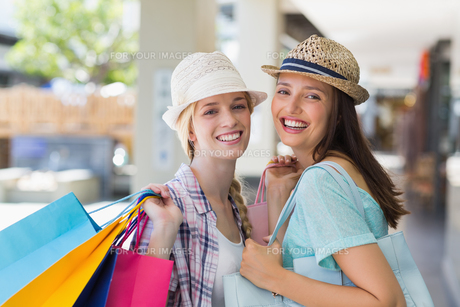 Happy women smiling at camera with shopping bagsの素材 [FYI00008987]